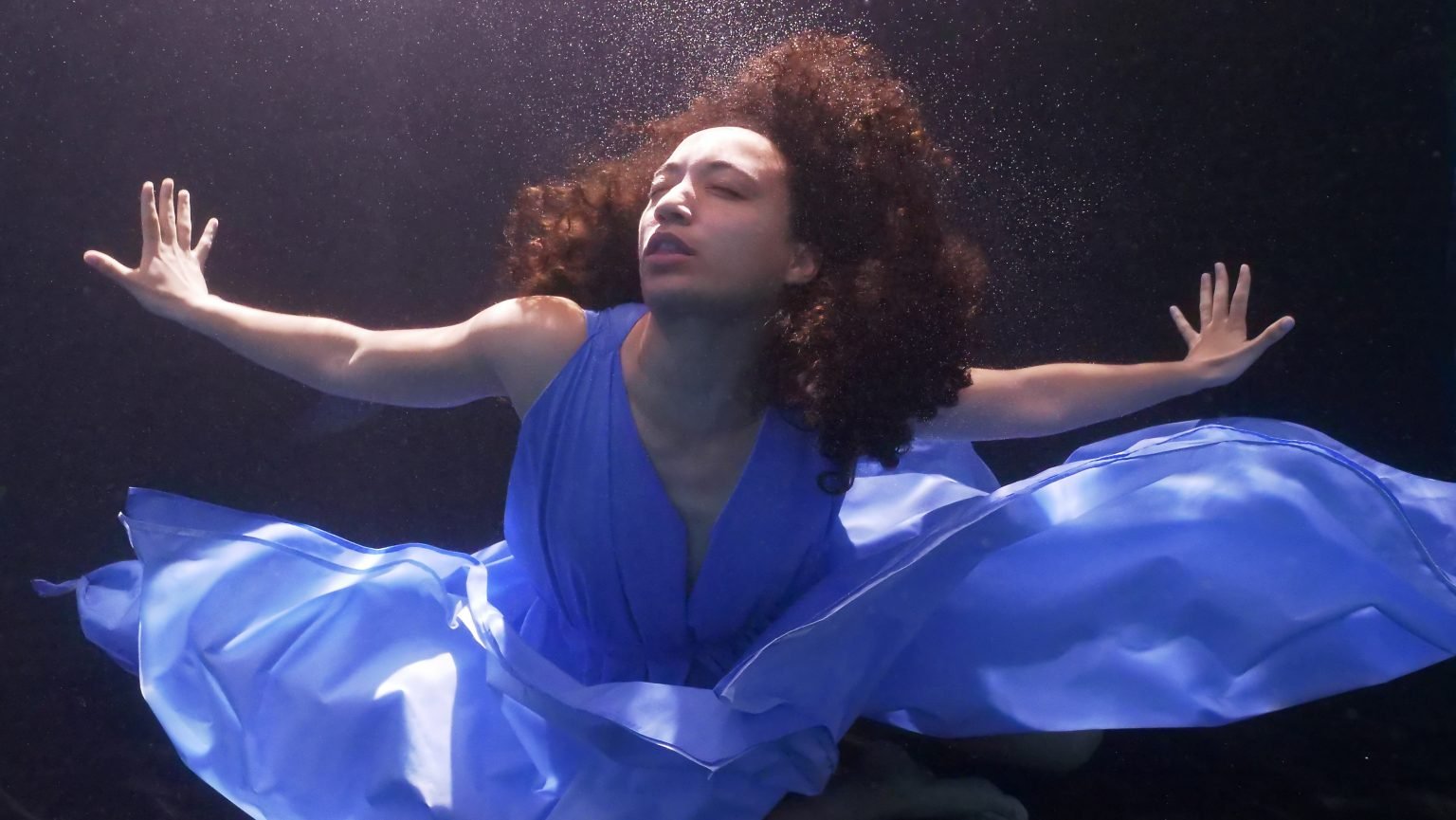A woman in a blue dress underwater with her arms stretched out