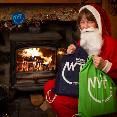A photo of Santa in front of a fire holding resource packs from North Yorkshire Together