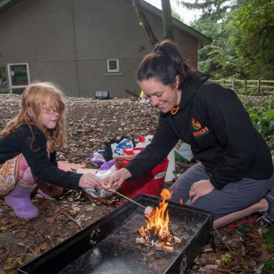 Rachael Muir showing youngsters how to use a camp fire safely at Embers holiday club at Catterick Garrison